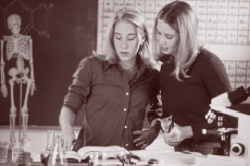 Sepia photograph of two high-school-aged girls performing a science experiment in school