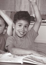 Photograph of a young boy raising his hand in 