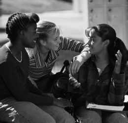 Black and white photograph of three girls sitting together and happily talking, probably in the hall at school
