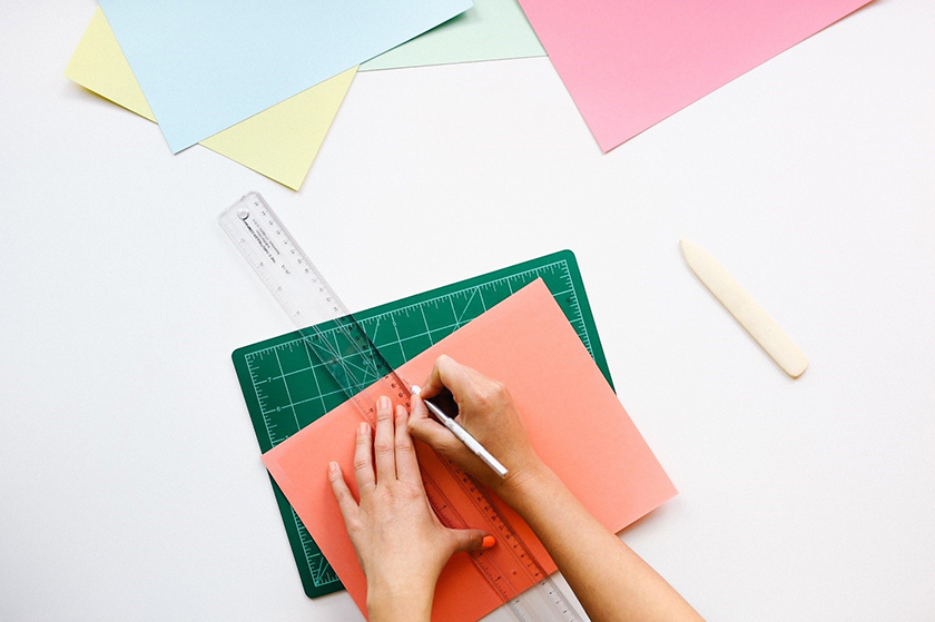 Image of a person using a knife to cut construction paper under against a ruler. There are other pieces of paper scattered about