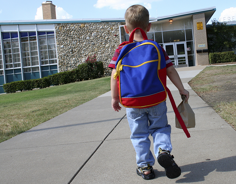 Young student walking to school wearing a backpack with a brown paper lunch bag in his hand
