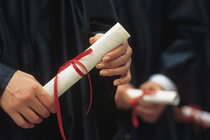 Photo of graduate holding diploma.