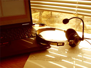 Image of a laptop computer, a pair headphones, and a printout of a reading passage.